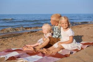Дети сидят на пляже плед песок море