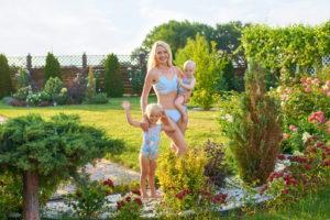 Красивая женщина в купальнике с дочками. Блондинки