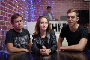 два парня и девушка музыканты в черном в кафе