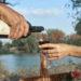 Реки мужчины и женщина с бутылкой вина и бокалом на фоне реки